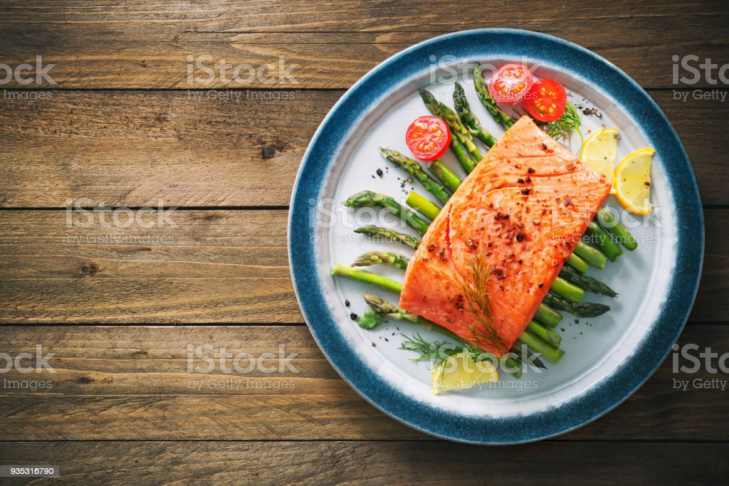 Grilled salmon garnished with green asparagus and tomatoes stock photo