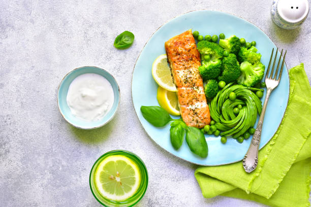 Grilled salmon garnished with green vegetables stock photo
