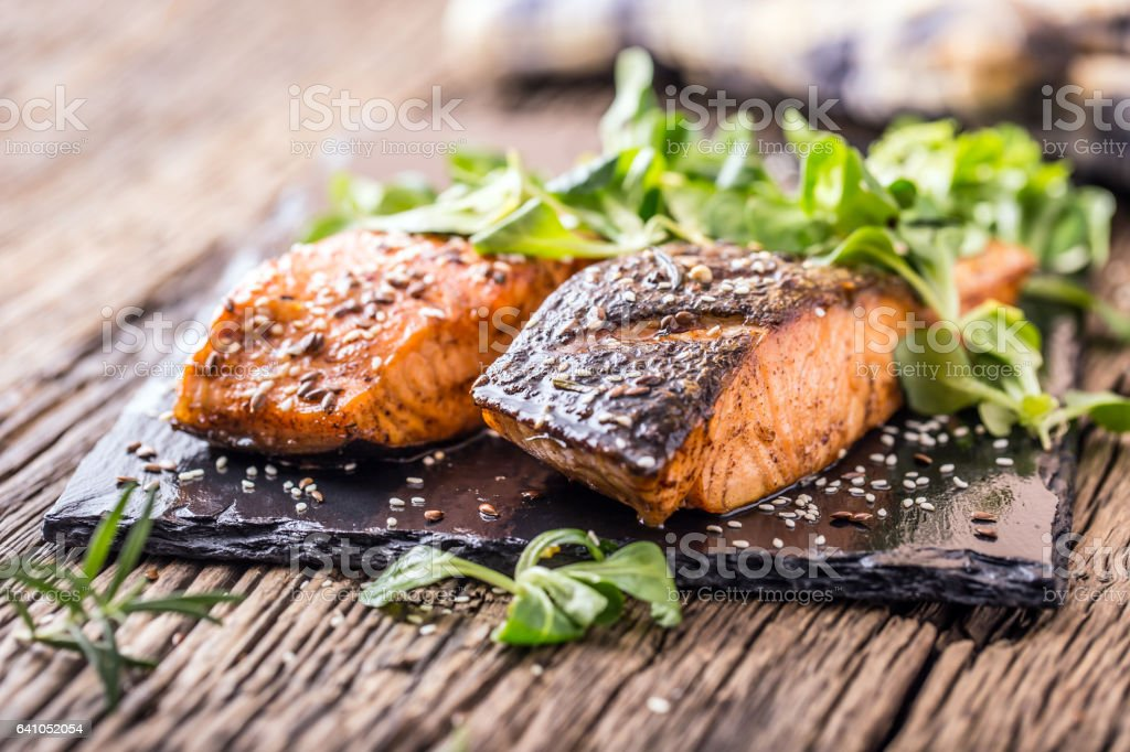 Grilled salmon herb decoration on vintage pan or slate board. stock photo