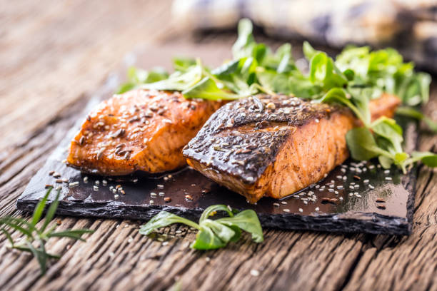 grilled salmon herb decoration on vintage pan or slate board. - sesame stock photos and pictures