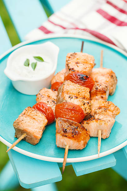 Grilled salmon kebabs with cherry tomatoes and garlic sauce stock photo