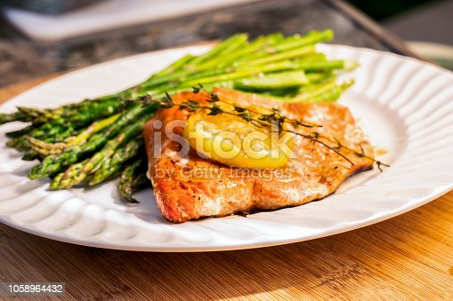 Beautiful salmon filet grilled and plated with lemon and asparagus