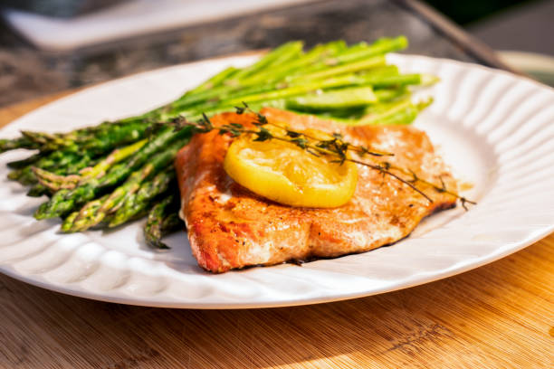 Grilled salmon on a plate with asparagus Beautiful salmon filet grilled and plated with lemon and asparagus ketogenic diet stock pictures, royalty-free photos & images