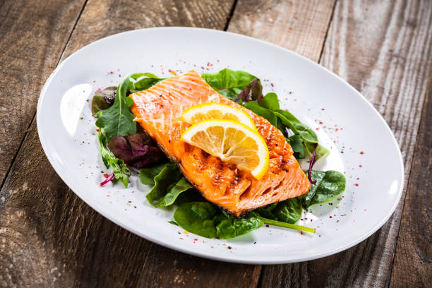 Grilled salmon on fresh vegetables on wooden table stock photo