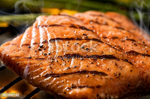 Close up of a grilled salmon filet on charcoal grill with asparagus, hot charcoal, fire and smoke.  Please see my portfolio for other food and drink images.