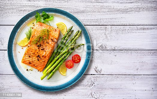 Grilled salmon steak garnished with green asparagus, lemon and tomatoes.Top view