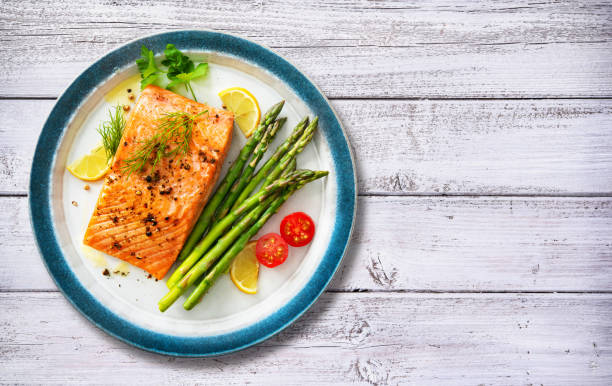 Grilled salmon steak garnished with green asparagus, lemon and tomatoes stock photo
