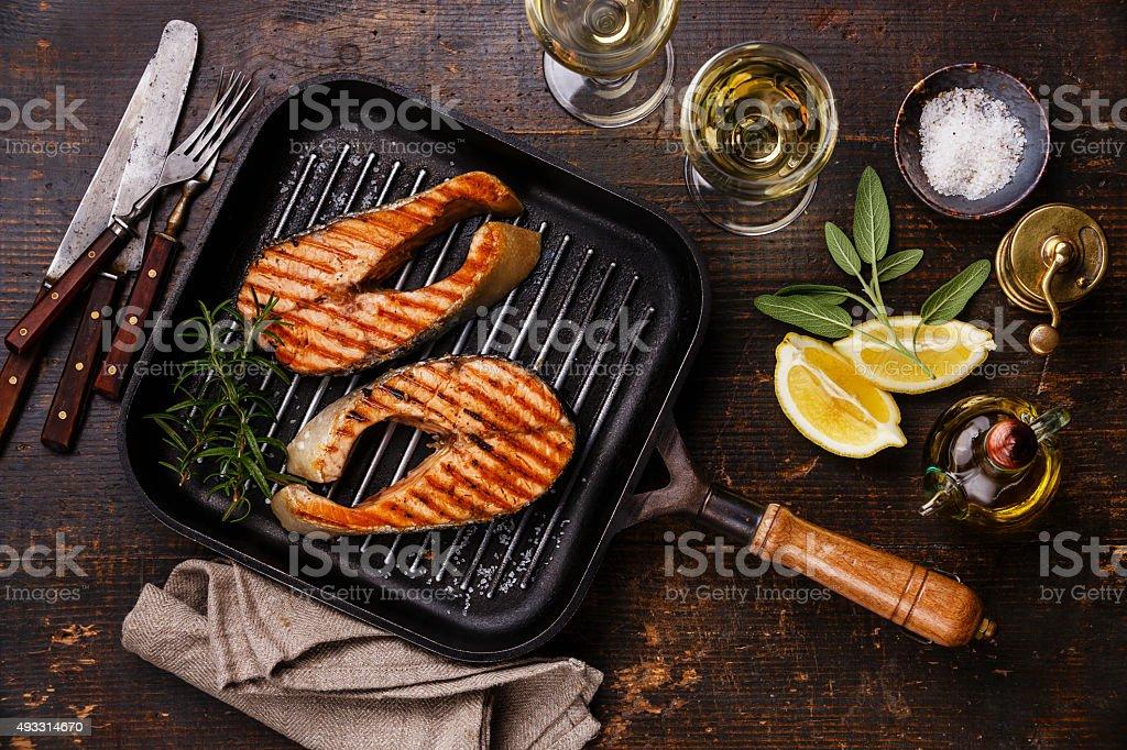 Grilled salmon Steak on grill pan with wine stock photo