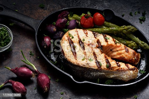Barbecue grilled salmon steak with vegetables in a skillet