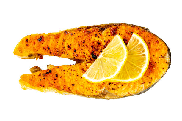 Grilled salmon steak with lemon slice isolated on a white background stock photo