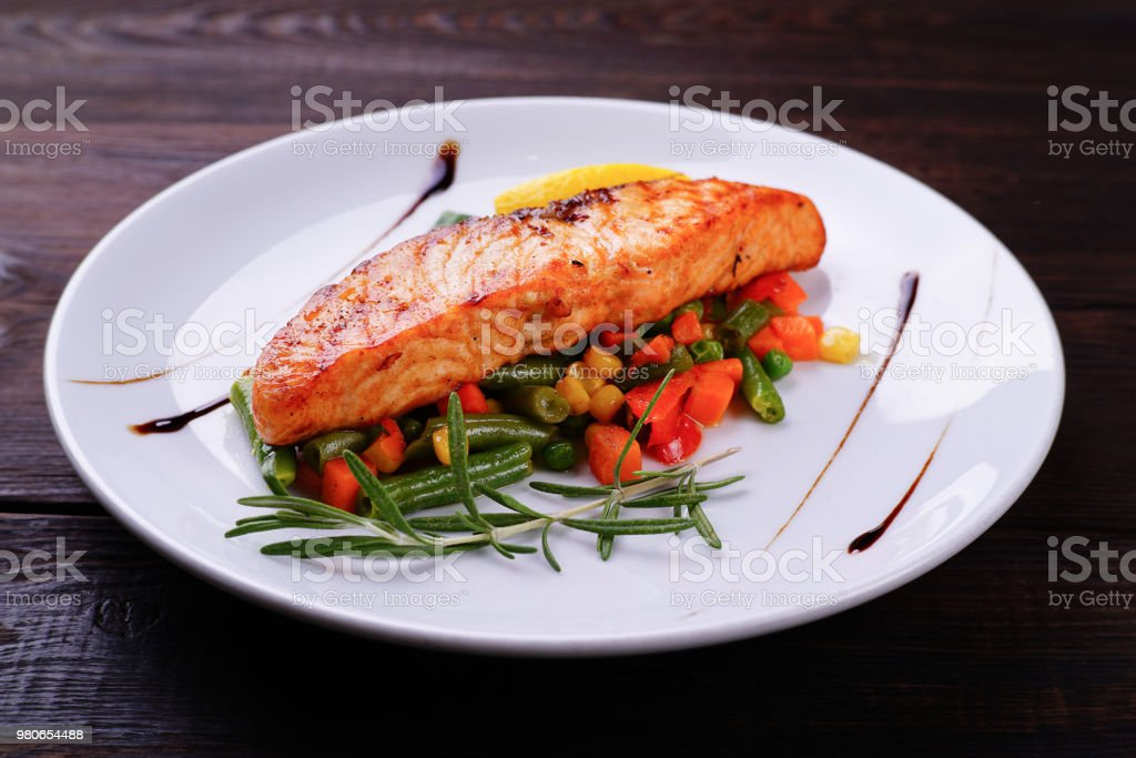 Grilled salmon steak with vegetable garnishing royalty-free stock photo