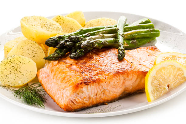 Grilled salmon with boiled potatoes and asparagus on white background