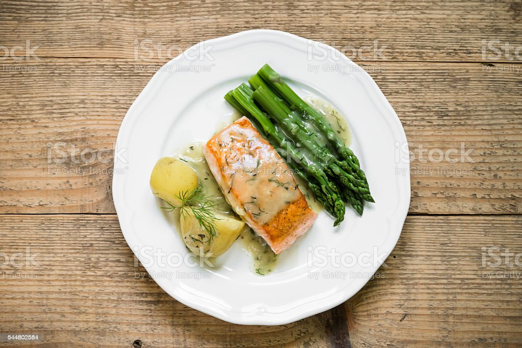 Grilled salmon with boiled potatoes and asparagus. Top view stock photo