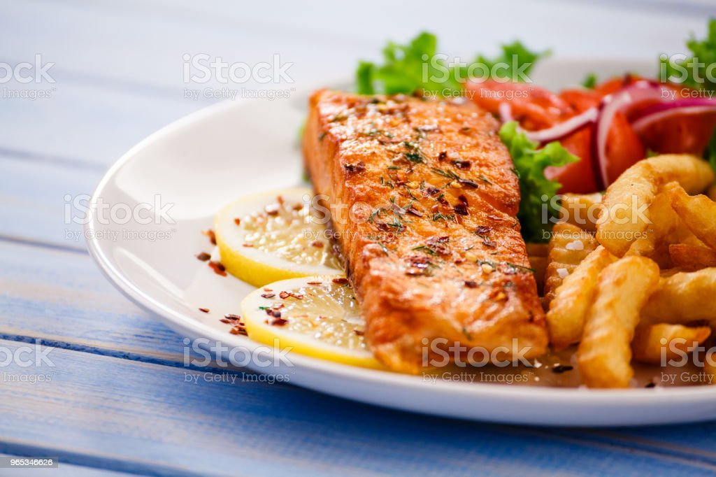 Grilled salmon with french fries and vegetables served on black stone plate on wooden table zbiór zdjęć royalty-free