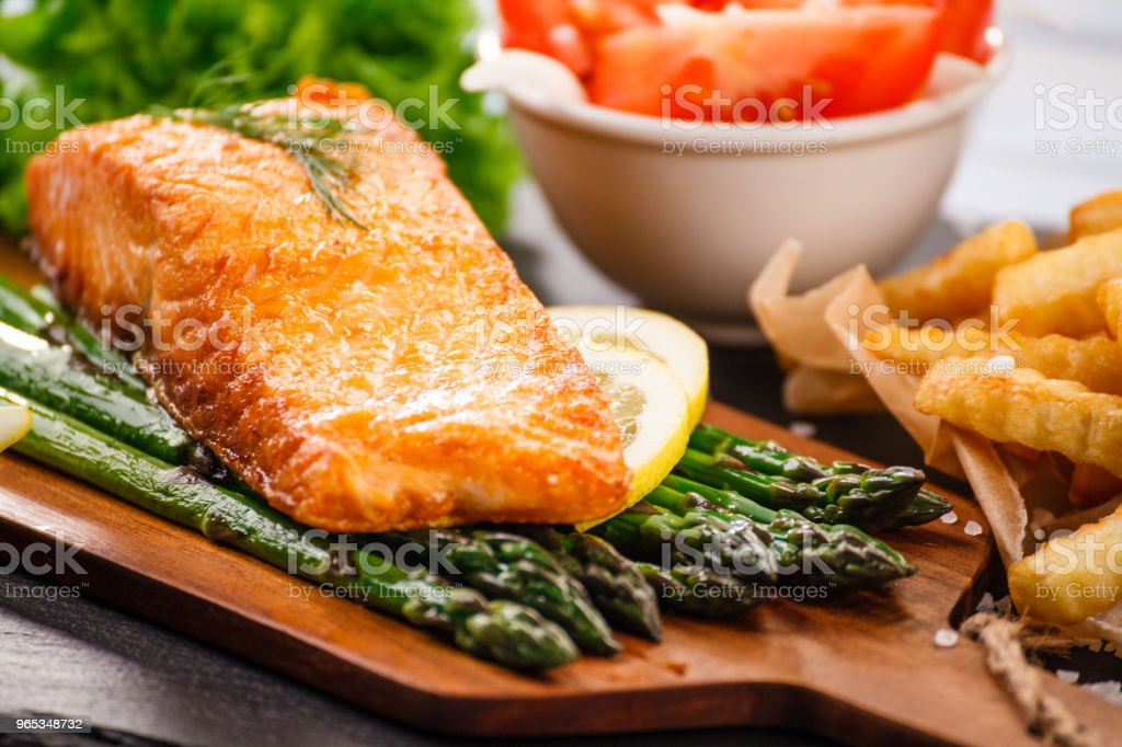 Grilled salmon with french fries and vegetables served on black stone plate on wooden table royalty-free stock photo