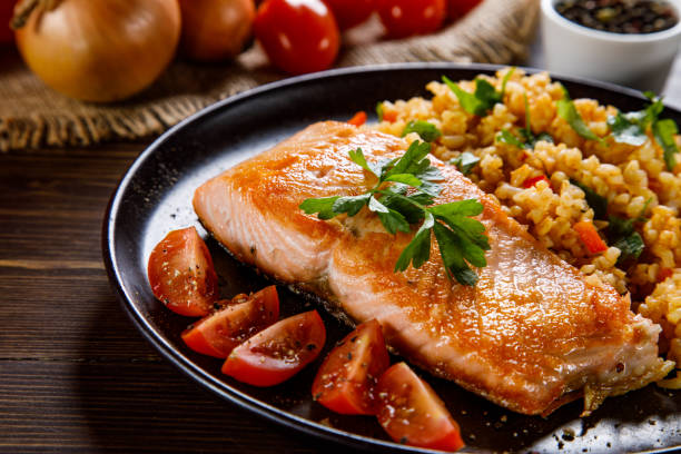 Grilled salmon with groats and vegetables Grilled salmon with groats and vegetables salmonidae stock pictures, royalty-free photos & images