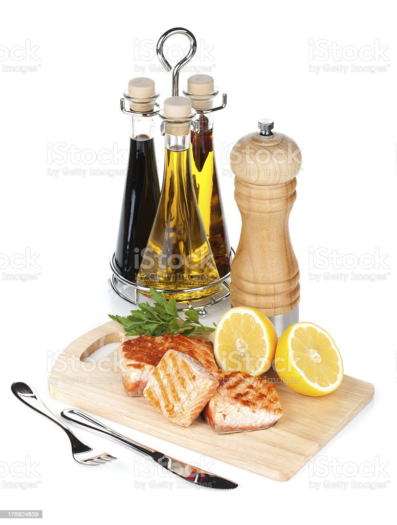 Grilled salmon with lemon and herbs on cutting board royalty-free stock photo