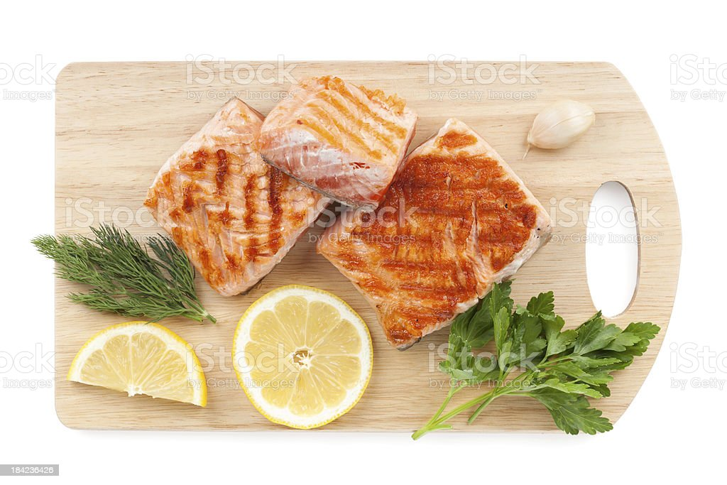 Grilled salmon with lemon slices and parsley on cutting board stock photo