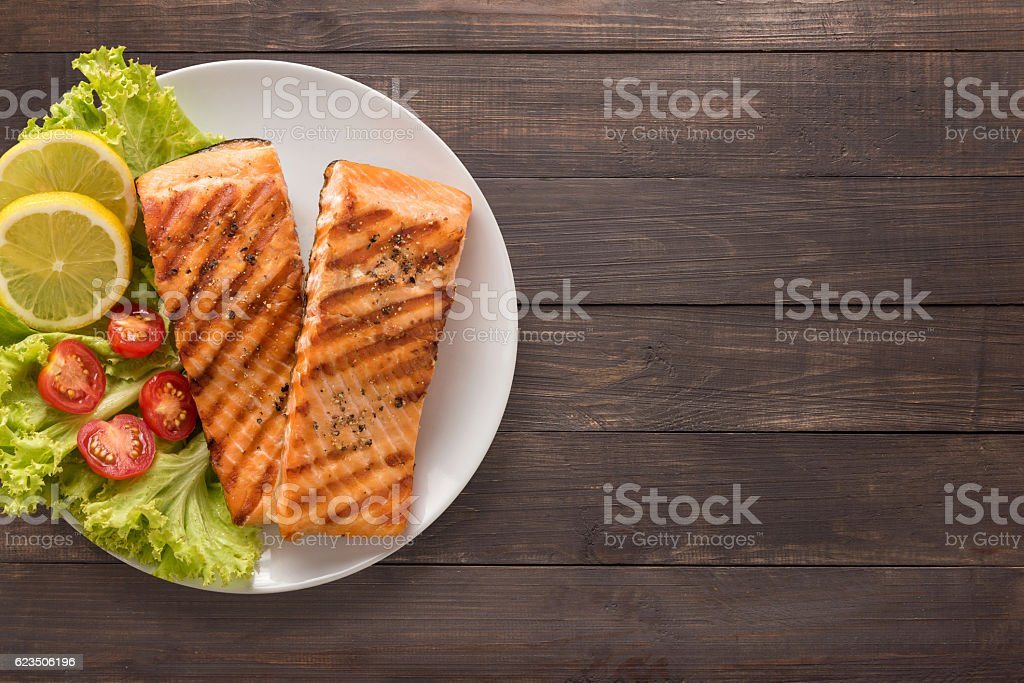 Grilled salmon with lemon, tomato on the wooden background. stock photo