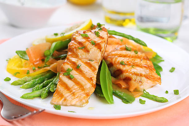 grilled salmon with spring vegetables on white plate, soft focus stock photo