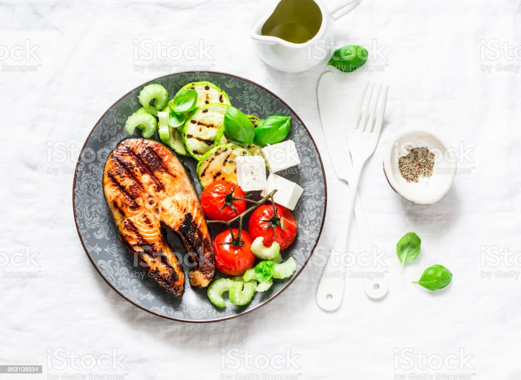 Grilled salmon, zucchini, baked cherry tomatoes and feta cheese - healthy balanced meal on light background, top view stock photo