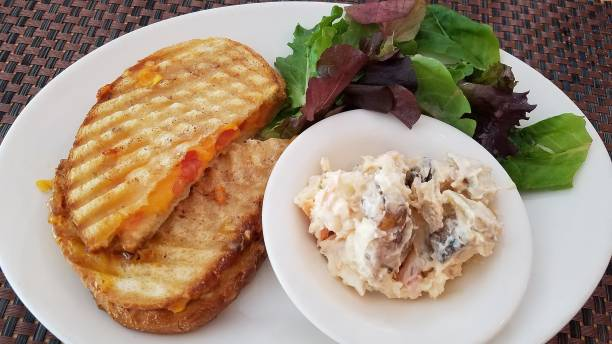 Grilled Sandwich, Green Salad and Potato Salad on Plate, Close Up stock photo