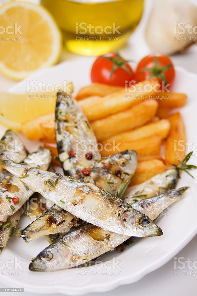 Grilled sardine fish and french fries royalty-free stock photo