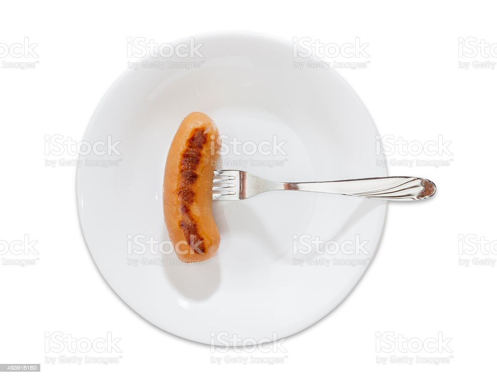 Grilled sausage impaled on a fork on a white dish stock photo