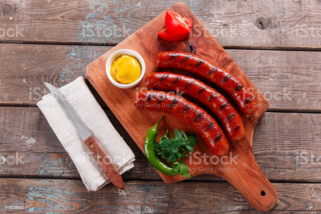 Grilled sausage on a wooden board with sauce and vegetables stock photo