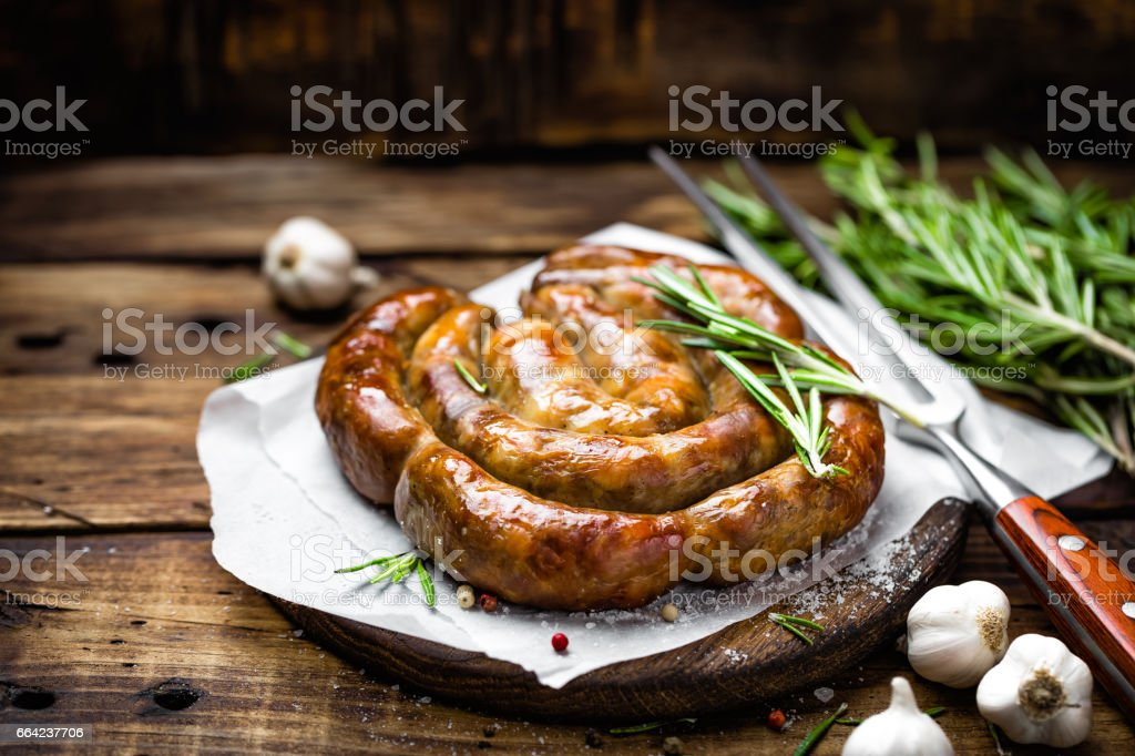 Grilled sausage on dark rustic wooden background stock photo