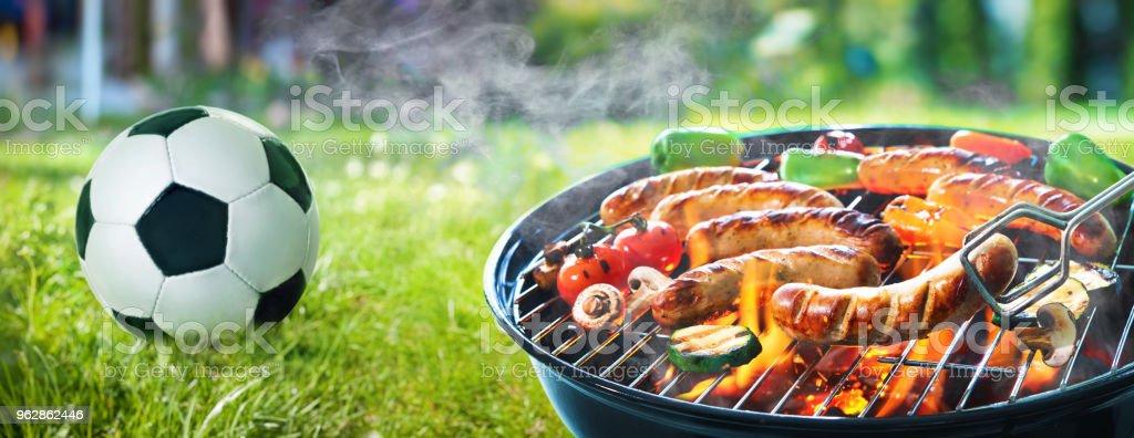 Saucisses grillées sur le grill enflammé et ballon de foot - Photo