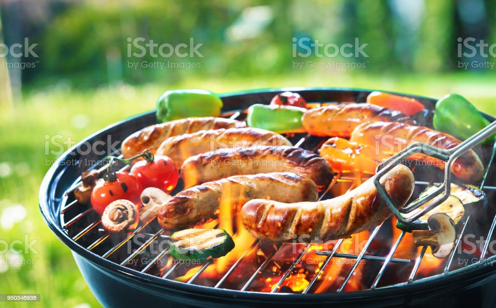 Grilled sausage on the flaming grill stock photo