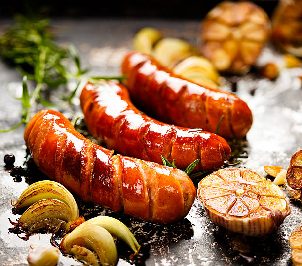 grilled sausage with garlic and onions - sausage stock photos and pictures