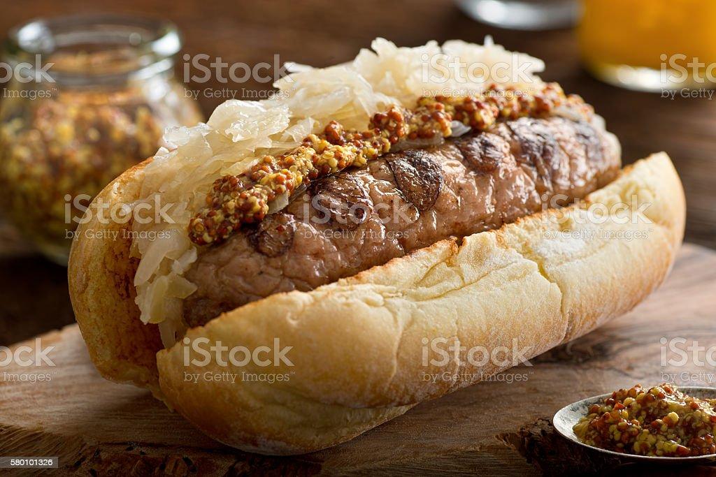 Grilled Sausage with Sauerkraut on a Bun bildbanksfoto