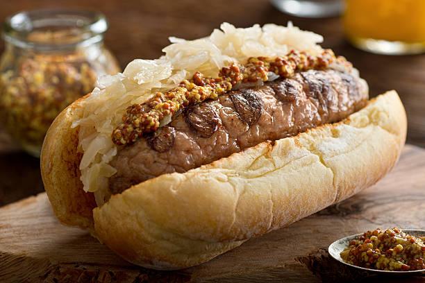 grilled sausage with sauerkraut on a bun - bratwurst mit sauerkraut stock-fotos und bilder
