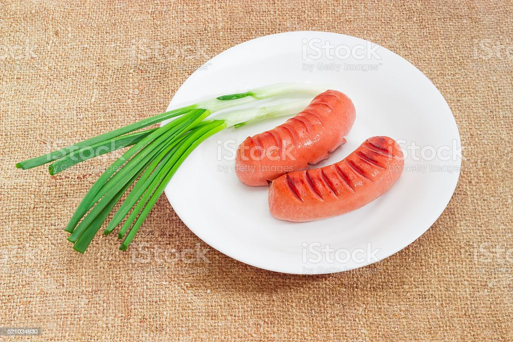 Grilled sausages and green onion on white dish on sackcloth stock photo