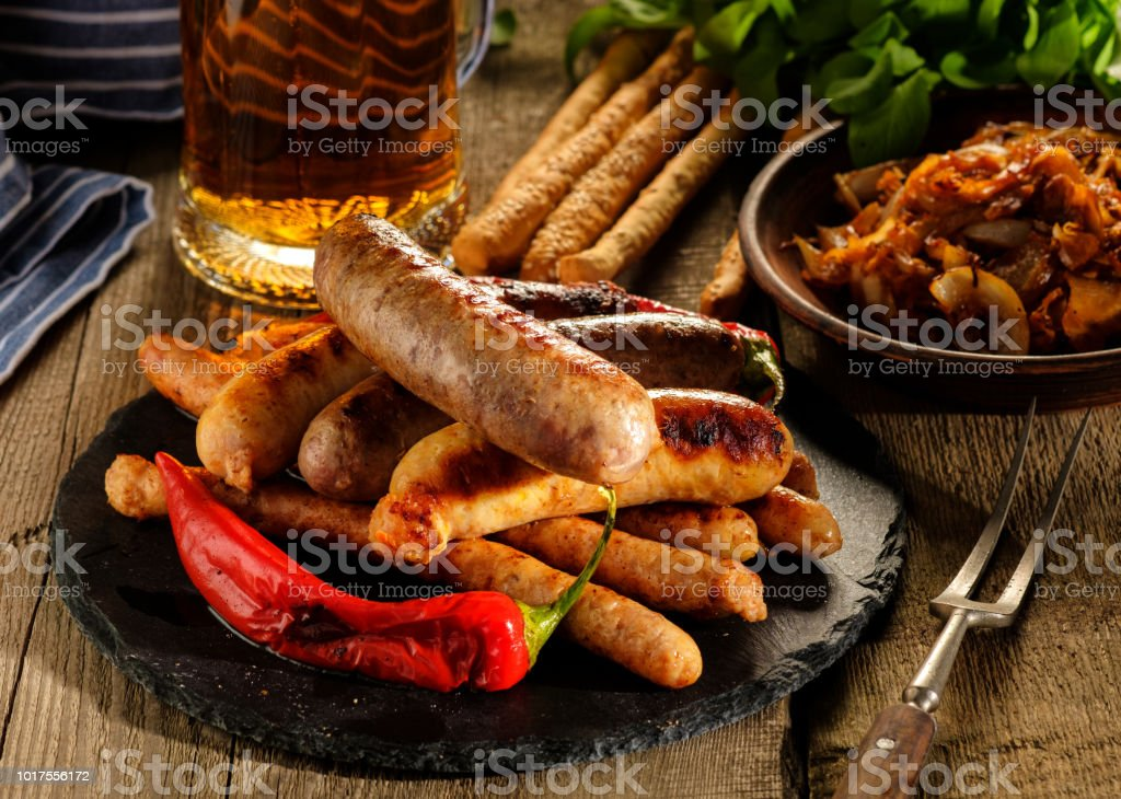 Grilled sausages and stewed cabbage with a mug of beer on a wooden table стоковое фото