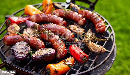 Grilled sausages and vegetables on a grilled plate, outdoor. Grilled food, bbq