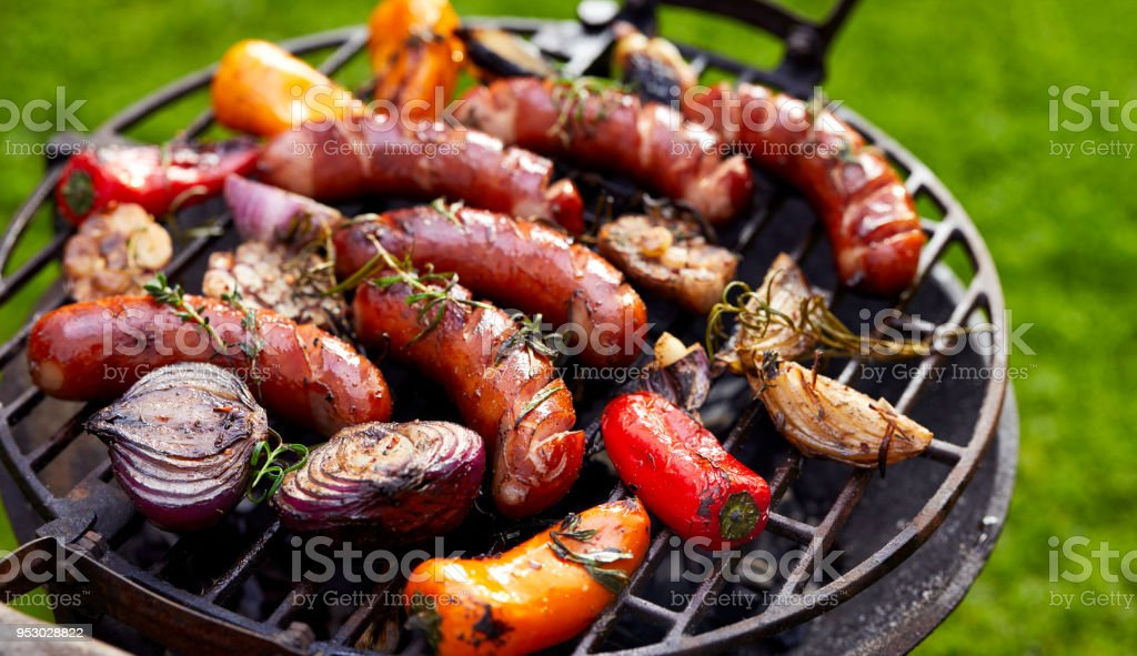 Grilled sausages and vegetables on a grilled plate, outdoor. stock photo