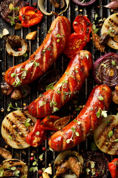 Grilled sausages and vegetables with addition spices and fresh herbs stock photo