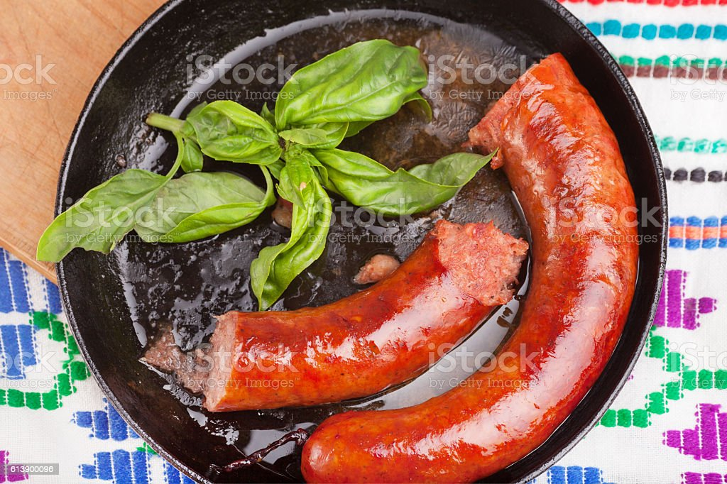 Grilled sausages in frying pan stock photo