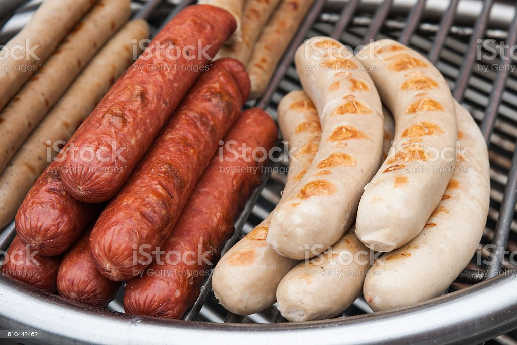 Grilled sausages on a metal grill stock photo