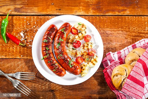 655794674 istock photo Grilled sausages on a white plate and wooden background 1017663512