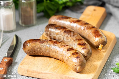 Grilled sausages on a wooden Board on a light gray kitchen table