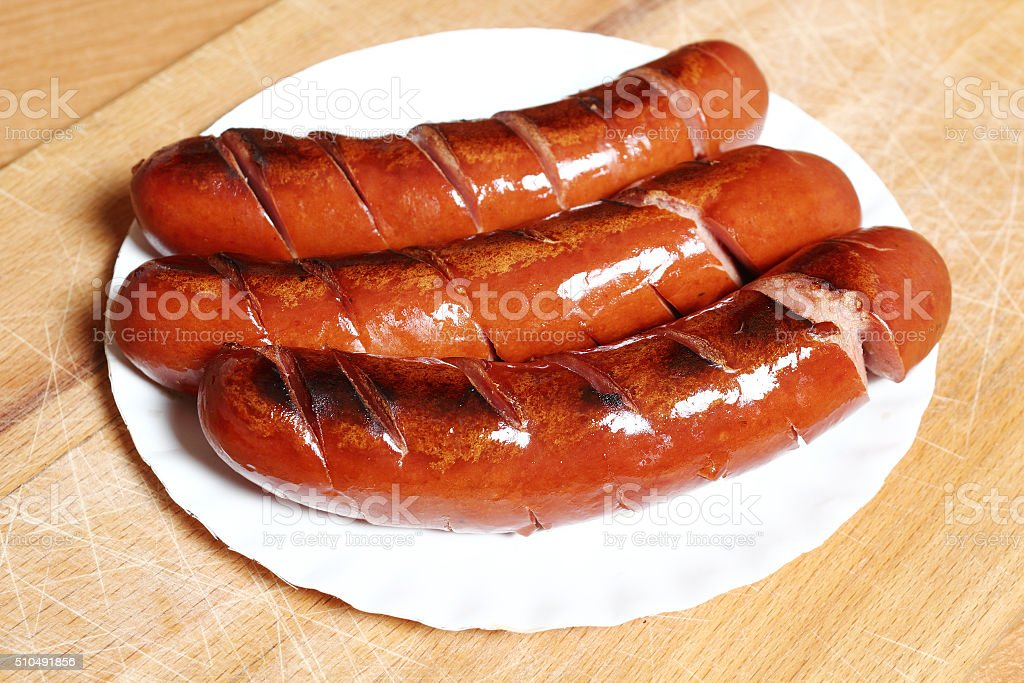 Grilled sausages on disposable paper plate stock photo