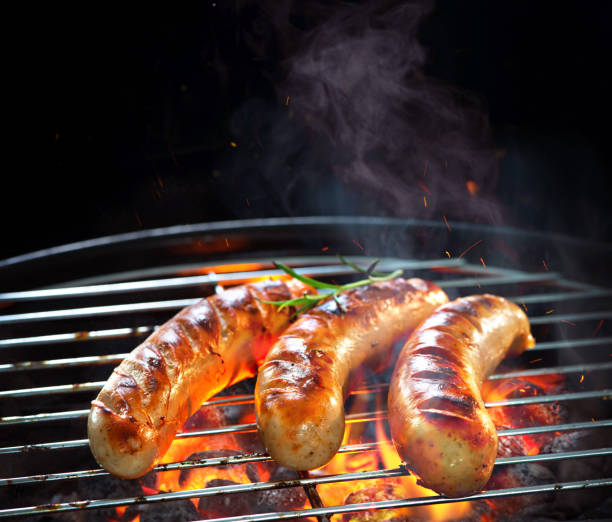 grilled sausages on grill with smoke and flame - sausage stock photos and pictures