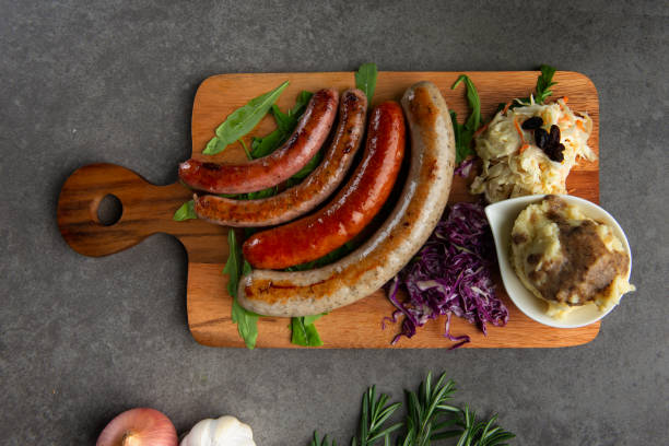 Grilled sausages on wooden board stock photo