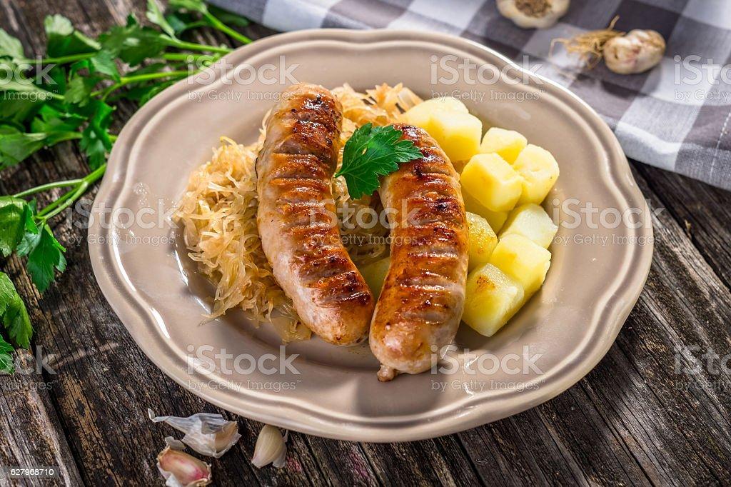 Grilled sausages,  potatoes and sauerkraut stock photo