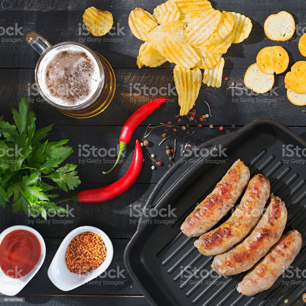 Grilled sausages with beer, chips and croutons. photo libre de droits