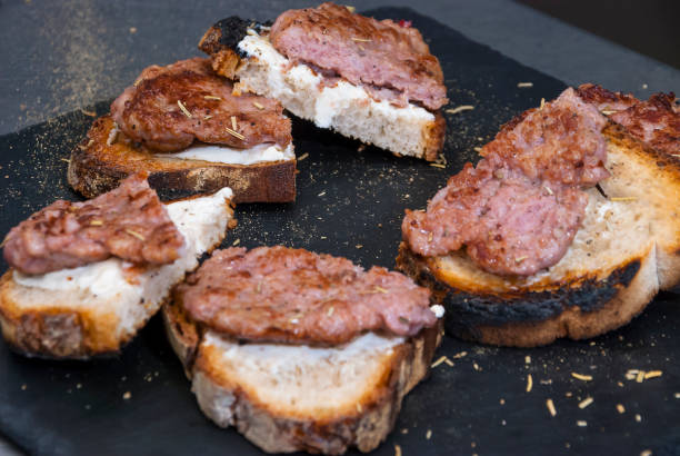 Grilled sausages with bread on black plate - foto stock